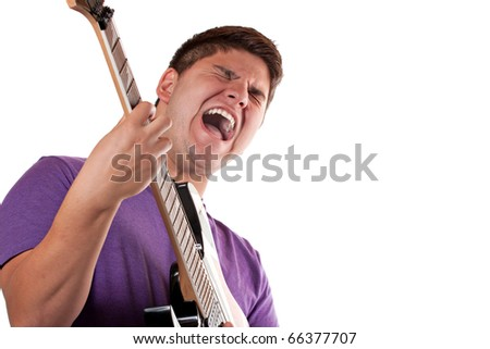 A man in his late teens rocks out while playing his electric guitar. - stock photo