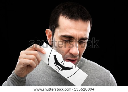 A man in his late thirties removes a fake smile (drawn on paper) revealing a sad, absent minded expression.