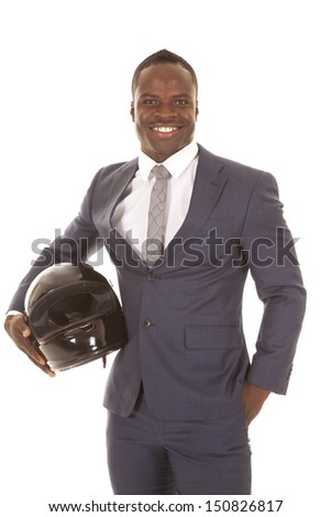 A man in his suit holding on to a helmet with a smile on his face.
