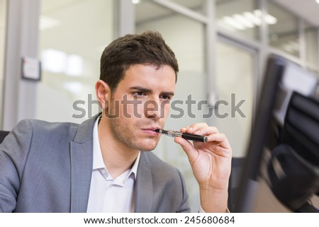 A man in office smoking with electronic cigarette