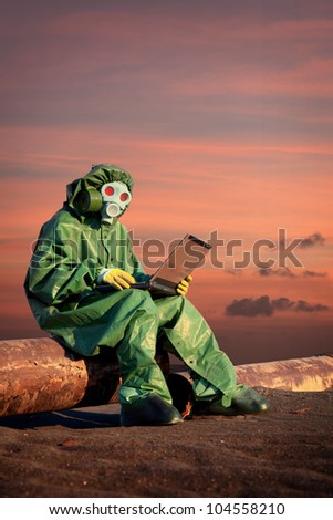 A man in protective suit works in the area of ??chemical contamination - stock photo