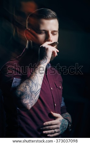 A man in red shirt smoking cigar. - stock photo