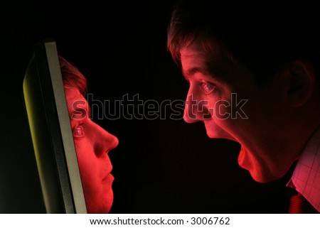 A man in shirt and tie screams at a red computer monitor as his own face emerges from it - stock photo
