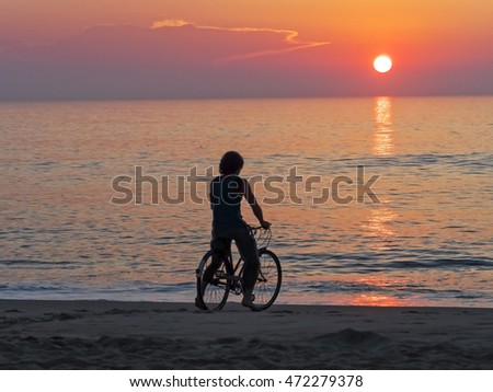 A man in silhouette on a bicycle watching the sunrise at the ocean.