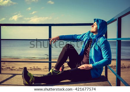 A man in sportswear relaxing on seashore. - stock photo