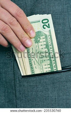 a man in suit getting dollar bills in the pocket of his jacket - stock photo