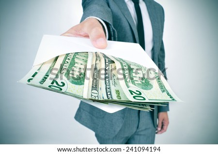 a man in suit giving an envelope full of american dollar bills - stock photo