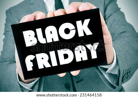 a man in suit showing a black signboard with the text black friday written in it - stock photo