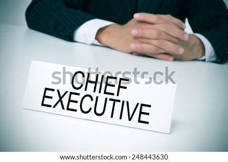 a man in suit sitting at a desk with a signboard in front of him with the text chief executive written in it - stock photo