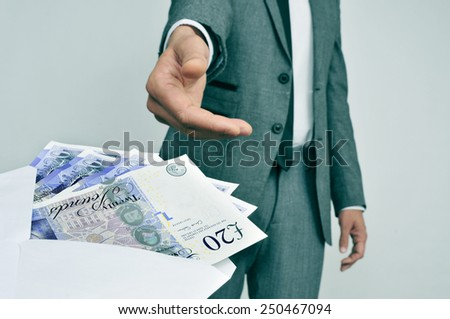 a man in suit taking an envelope full of pound sterling bills - stock photo