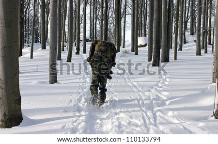 A Man in the Uniform Walking Through Winter Forest with Snowshoes (Winter Survival) - stock photo