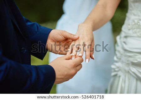a man in tuxedo placing a wedding ring on a womans hand as in a wedding ceremony