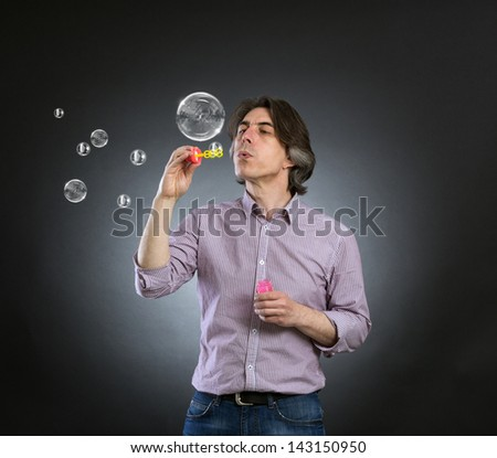 A man inflates soap bubbles. - stock photo