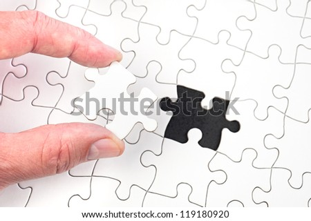 A man inserting the final puzzle piece of a white jigsaw.