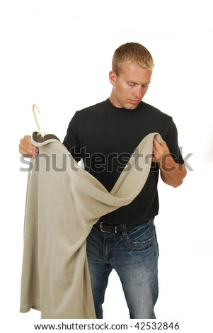 A man inspecting a new shirt to buy - stock photo