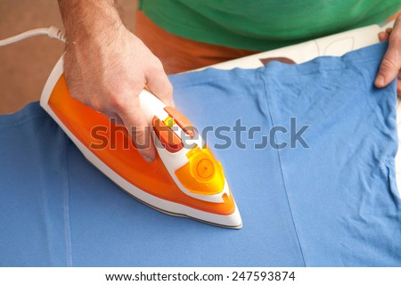 a man ironing clothes on ironing board