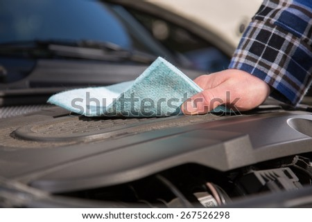 A man is cleaning his car engine with a cloth. - stock photo