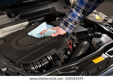 A man is cleaning his car engine with a rag. - stock photo