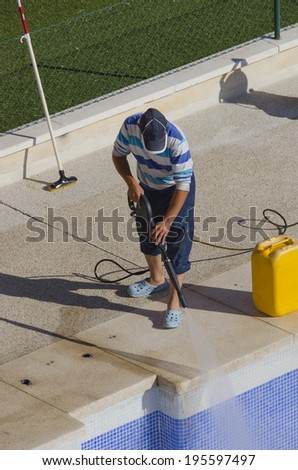 A man is cleaning the pool side with a pressure pump
