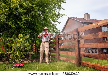 A man is cleaning wooden fence with electric power washer - stock photo