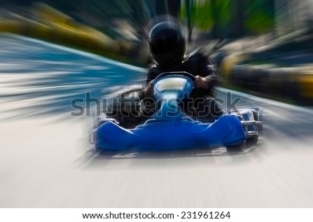 A man is driving Go-kart with speed in the park on karting track - front view. - stock photo