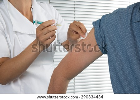 A man is getting an injection with a syringe at hospital - stock photo