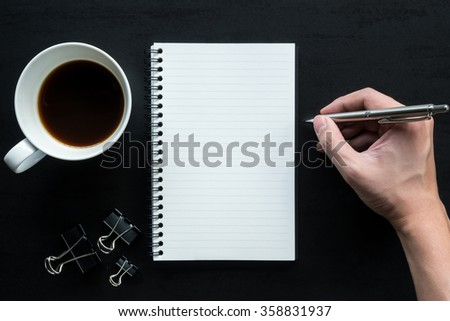A man is going to write something on a notebook using a pen. Black office table with a cup of coffee and supplies. Top view.