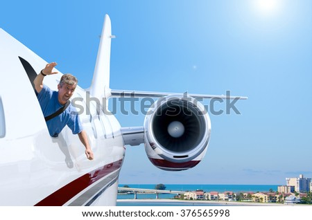 A man is hanging out of a private jet airplane window with a smile on his face as he waves hello as the plane is coming into a coastal airport. - stock photo