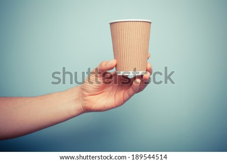 A man is holding a brown paper cup - stock photo