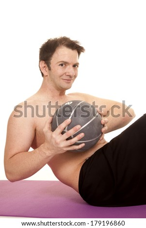 A man is holding a medicine ball working his abs. - stock photo