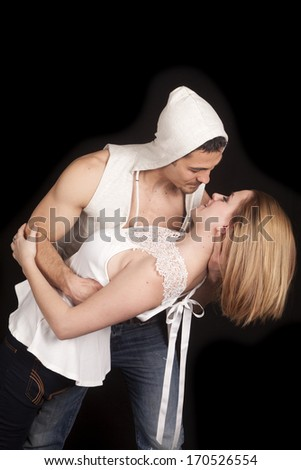 A man is holding a woman and he is about to kiss her.