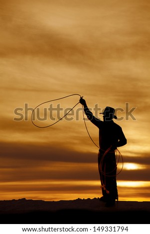 A man is in the sunset swinging a rope. - stock photo
