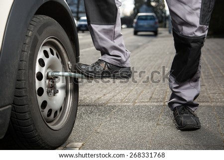 A man is loosening the screws from the tire. - stock photo