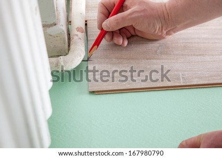 A Man is marking a piece of laminate before cutting. - stock photo