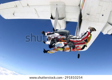 A man is not afraid to jump on a plane , launching in the clouds. Skydiving. - stock photo