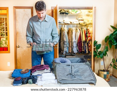 A man is packing his suitcase for a trip - stock photo