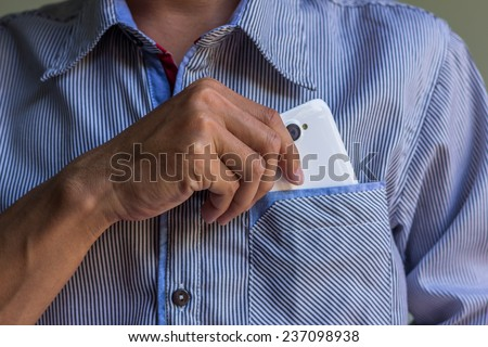 A man is picking up his smart phone - stock photo