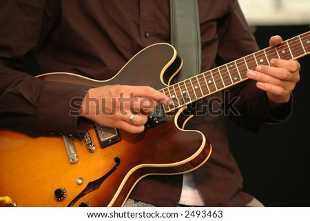 A man is playing his guitar.