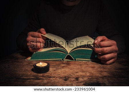 A man is reading a big book by candle light at night - stock photo