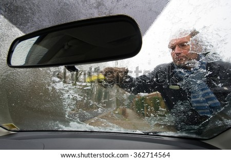 A man is scraping the ice from the windscreen of his car - stock photo