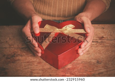 A man is sitting at a table and is holding a heart shaped box - stock photo