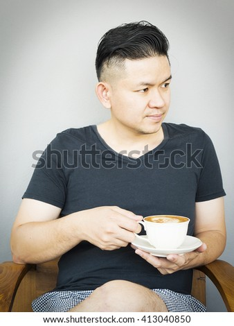 A man is sitting with coffee cup in his hand