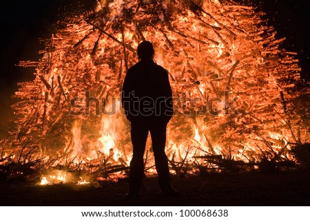 A man is standing close at a huge bonfire, a tradition with easter in Nort-West Europe. - stock photo