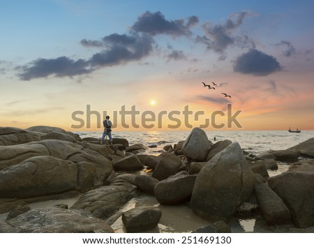 A man is standing on a rock with a camera shooting and Sunset over the sea at rayong,Thailand - stock photo