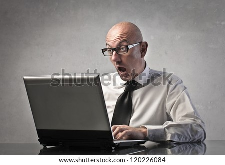 A man is surprised while using a computer - stock photo