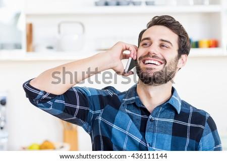 A man is talking on the phone and smiling at work - stock photo