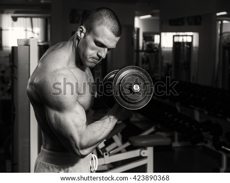 A man is training in gym with dumbbells. A healthy lifestyle and body care