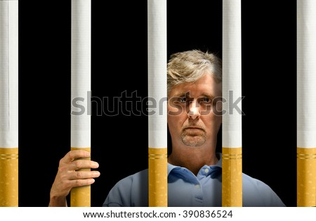 A man is trapped behind a prison of cigarettes representing nicotine addiction, depression and the struggle to quit smoking. - stock photo