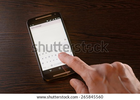 A man is typing an sms on the keypad of his black smartphone - stock photo