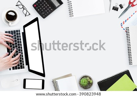A man is typing on a laptop on a full messy table. Top view with copy space in the middle. - stock photo